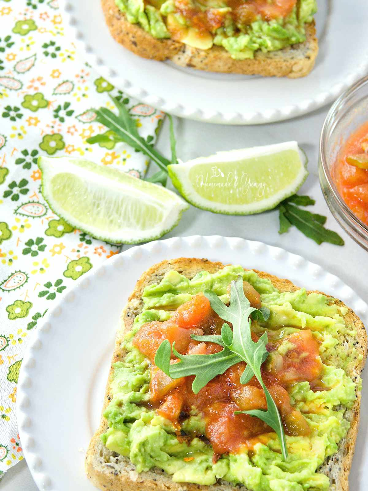 Mashed avocado on toast, topped with salsa and arugula.