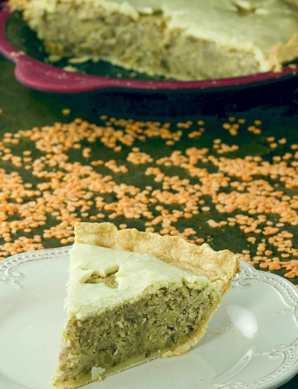 A slice of Red Lentil Tourtiere Pie on an ivory plate.