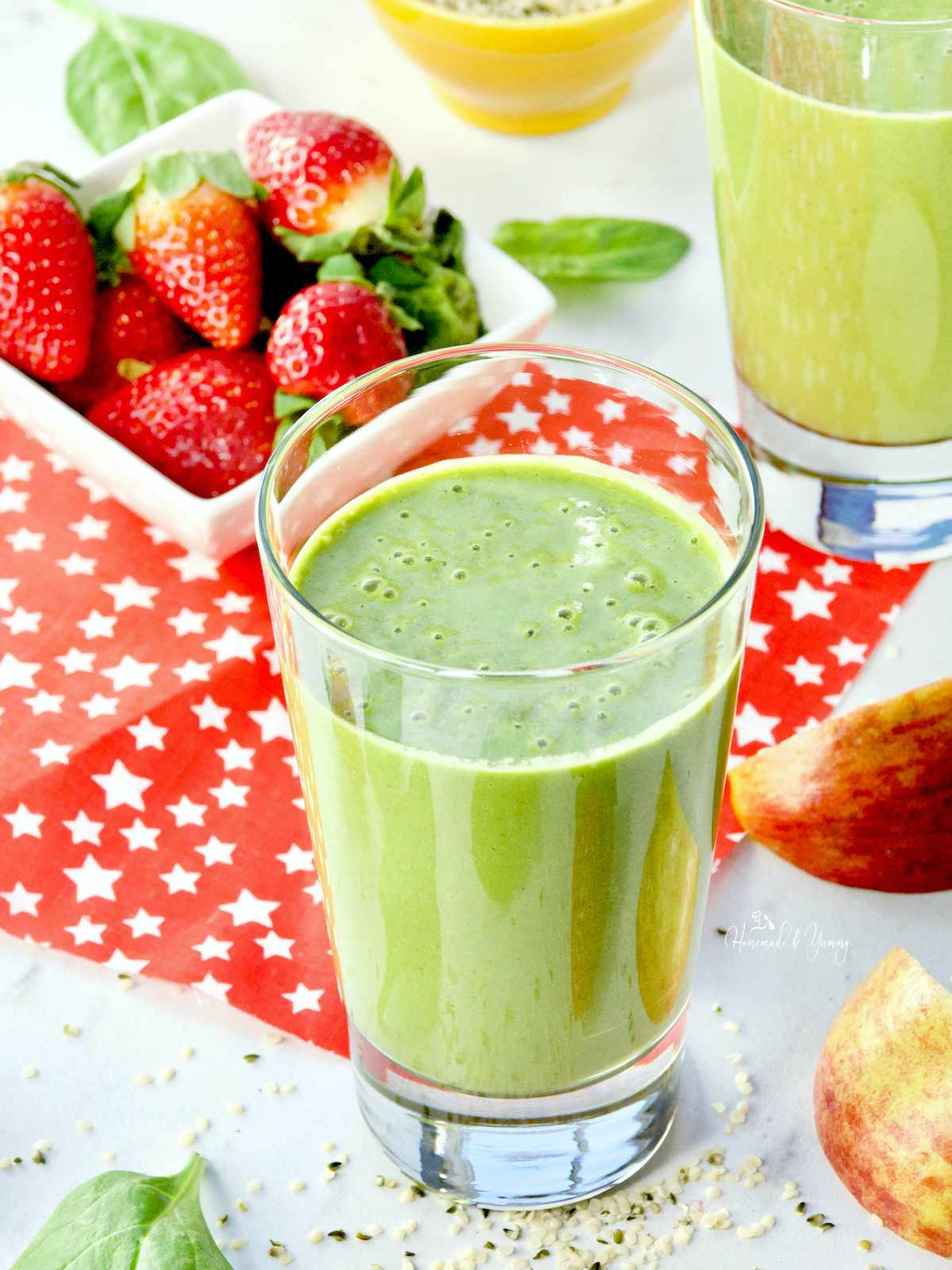 Green Hemp Smoothie in a glass, strawberries and apple slices in the background.