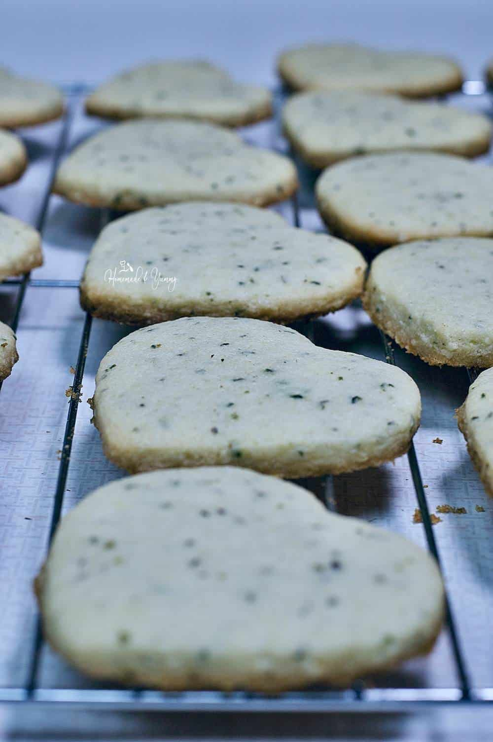 Fresh baked heart shaped cookies with hemp seeds cooling on a rack