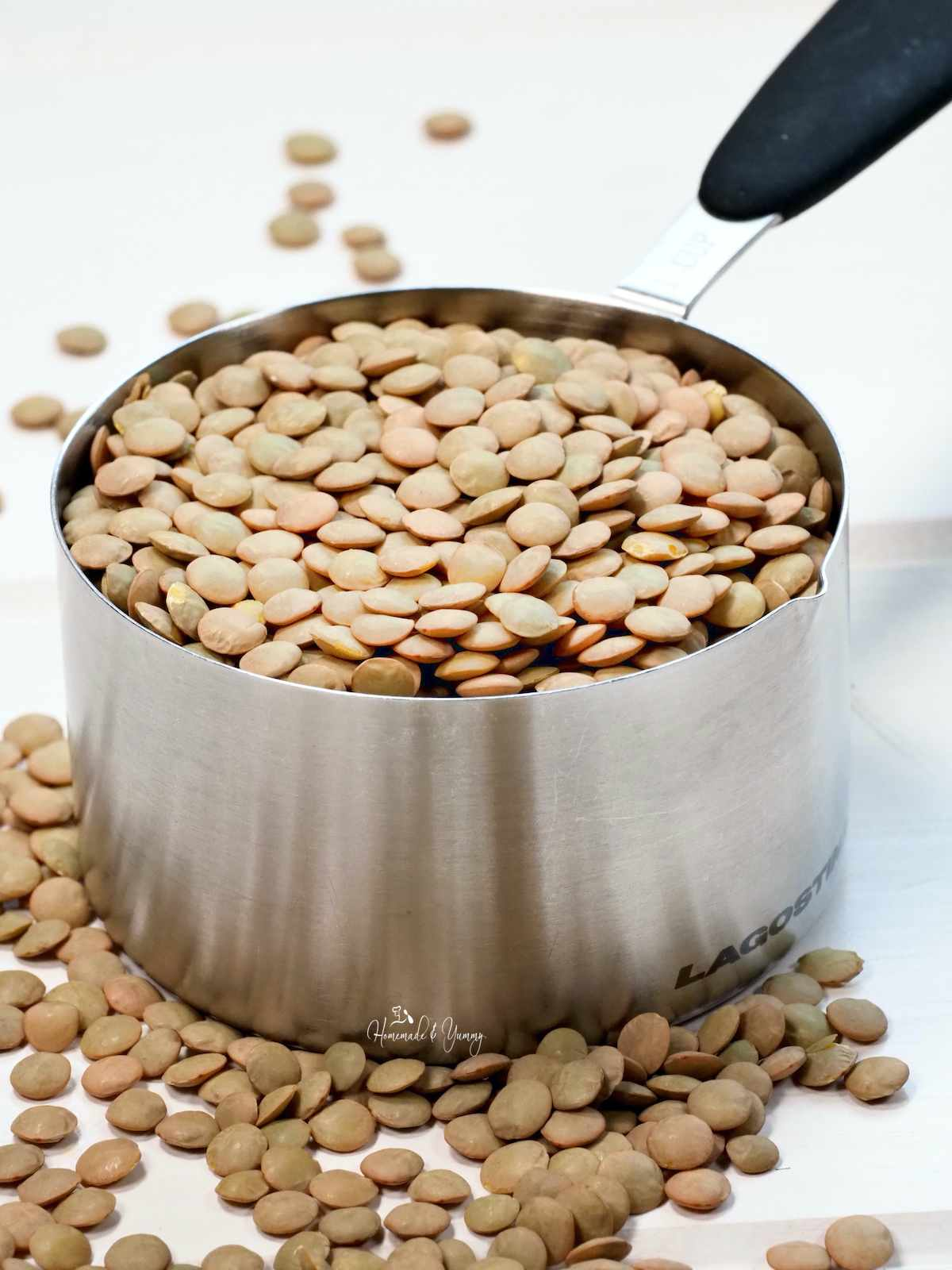 A measuring cup of dry lentils ready to cook