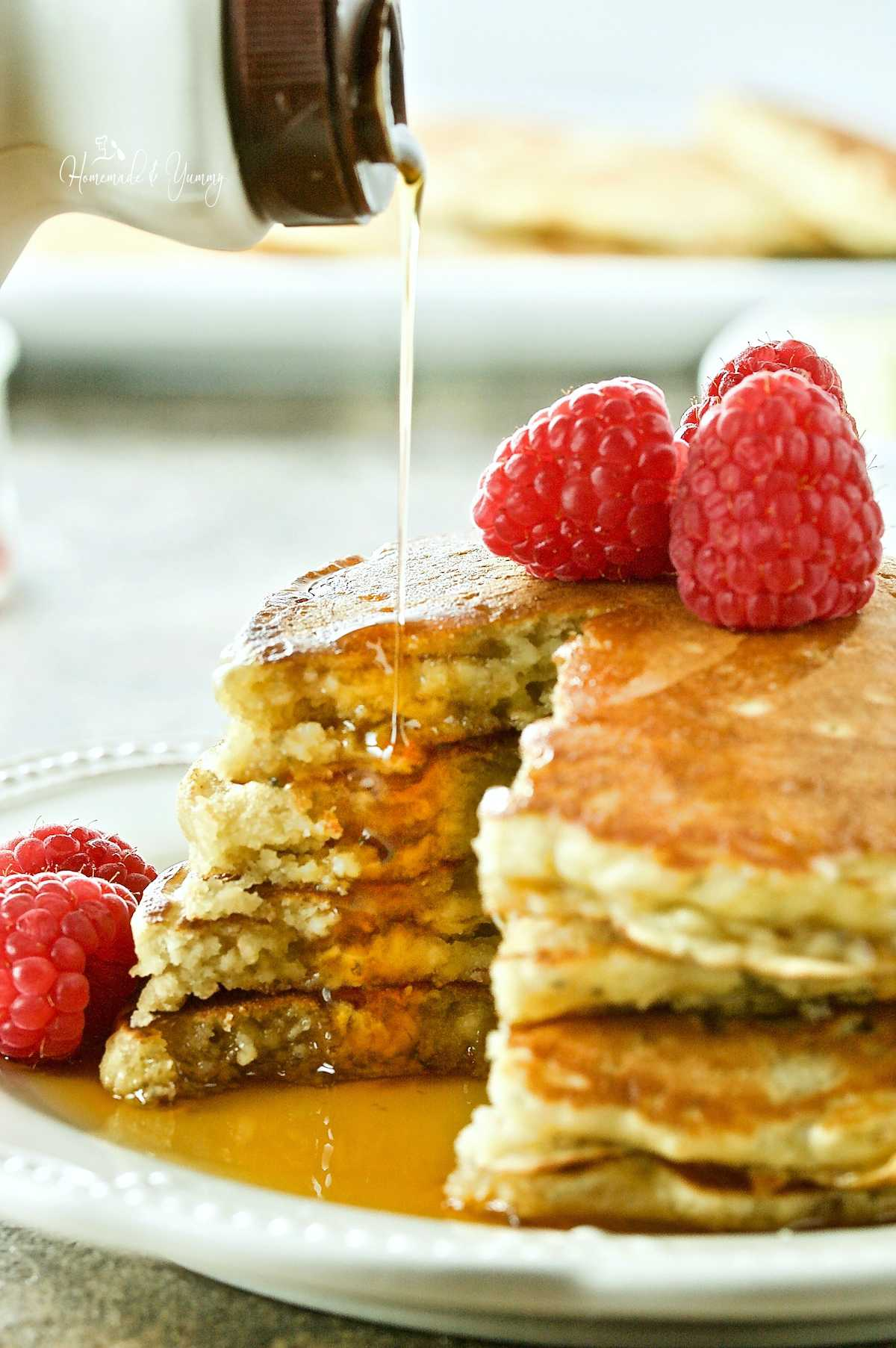 Syrup getting poured over a stack of oatmeal pancakes, topped with raspberries.