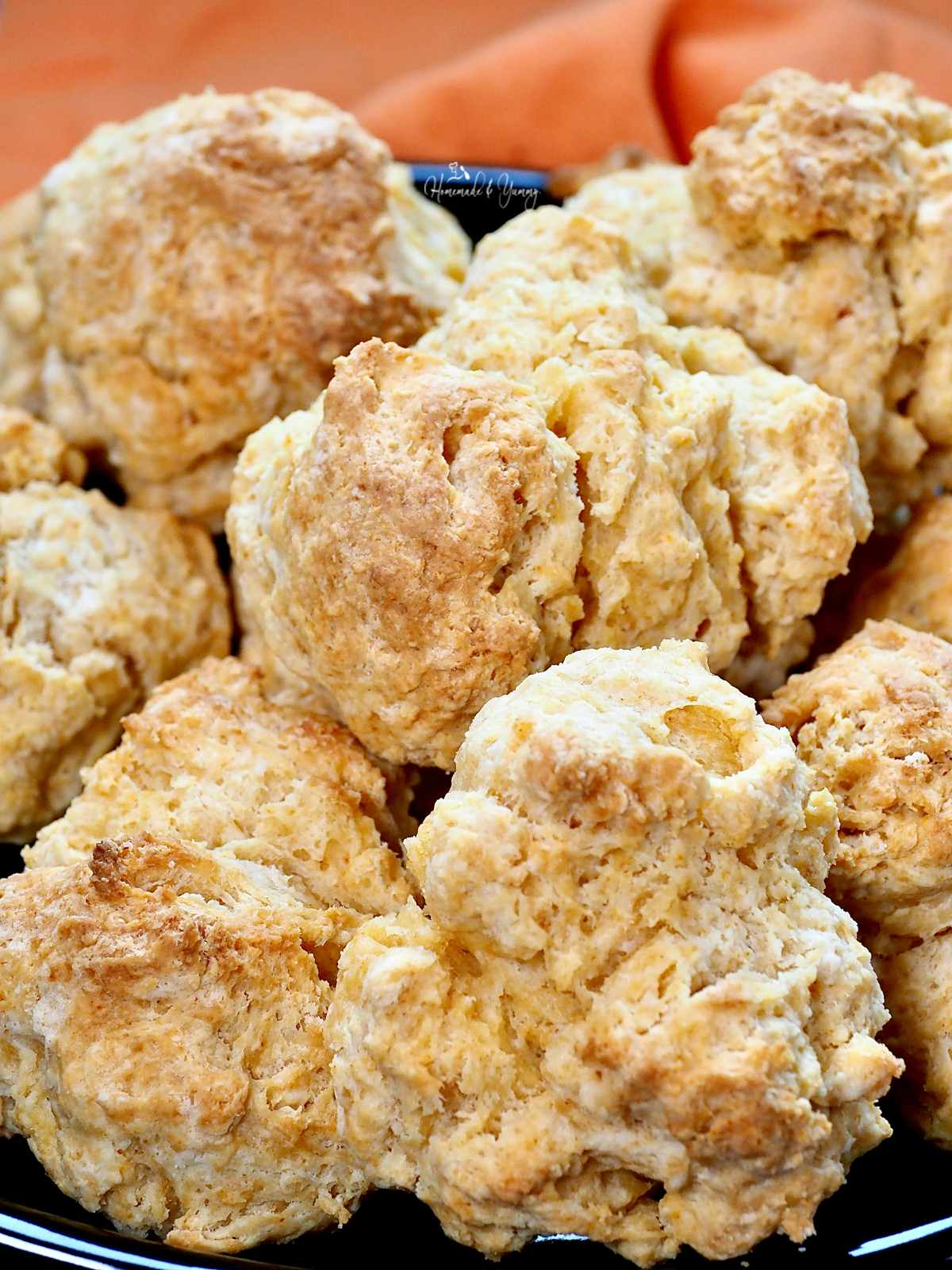 A pile of gramma's biscuits on a plate.