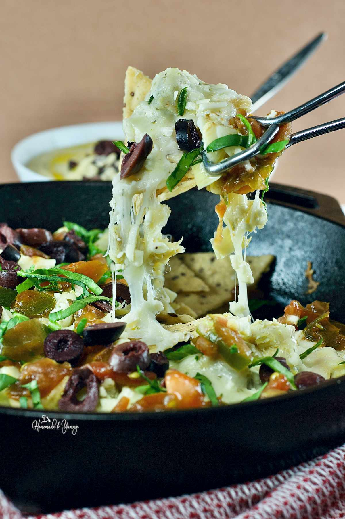A pan Greek nachos, with a bowl of hummus in the background.
