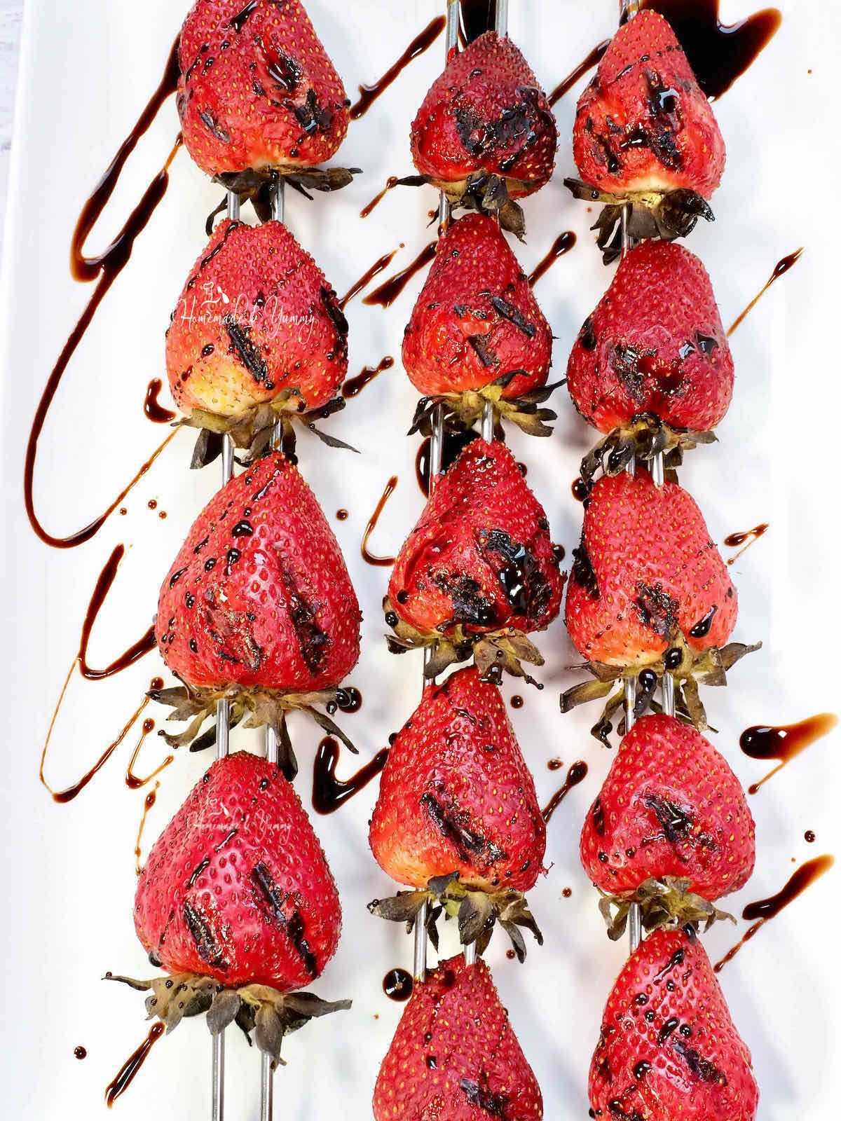 Grilled Strawberry Kabobs on a white plate drizzled with balsamic.
