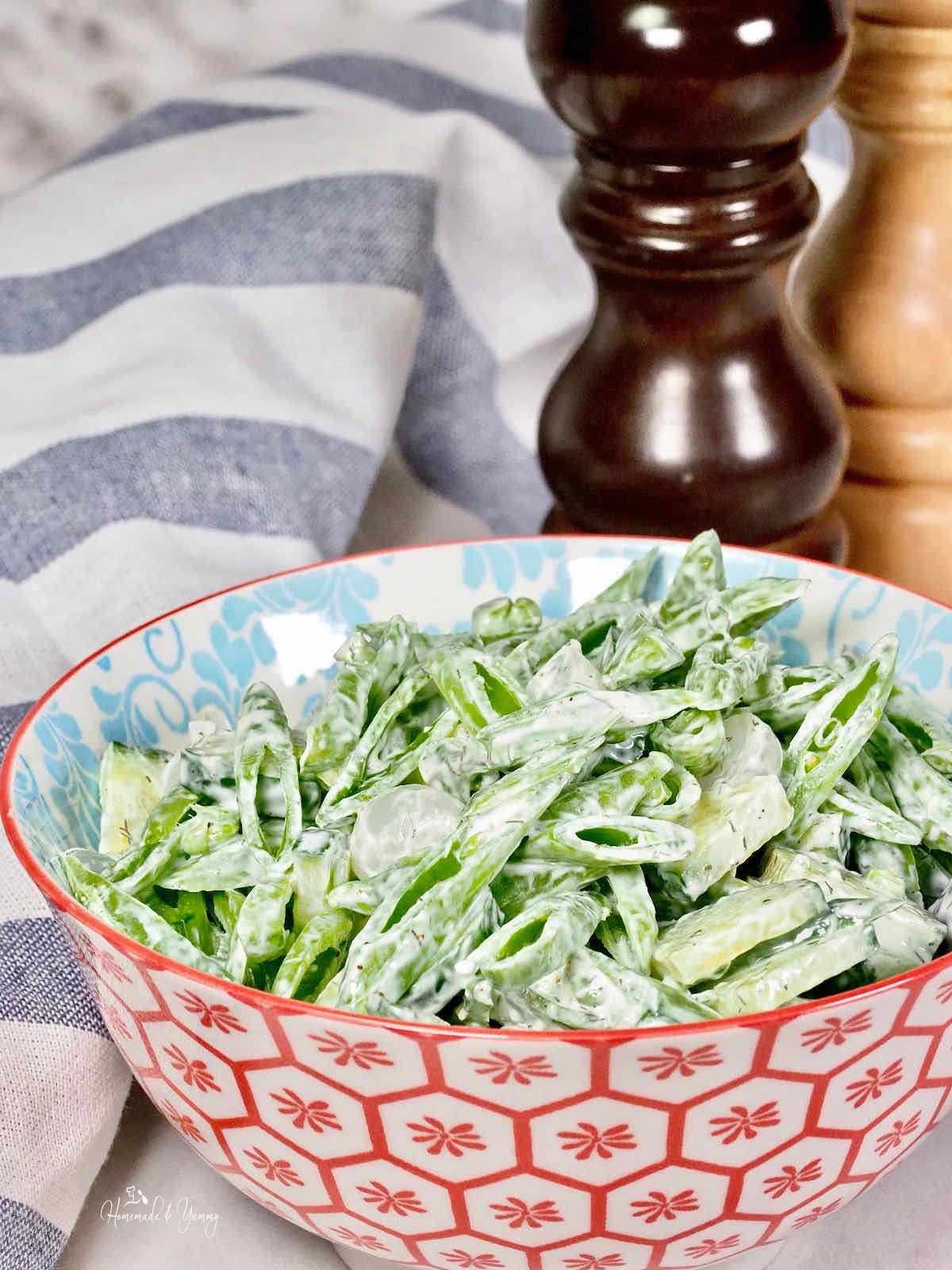 A bowl of snap pea salad with cucumber and pickled onions.