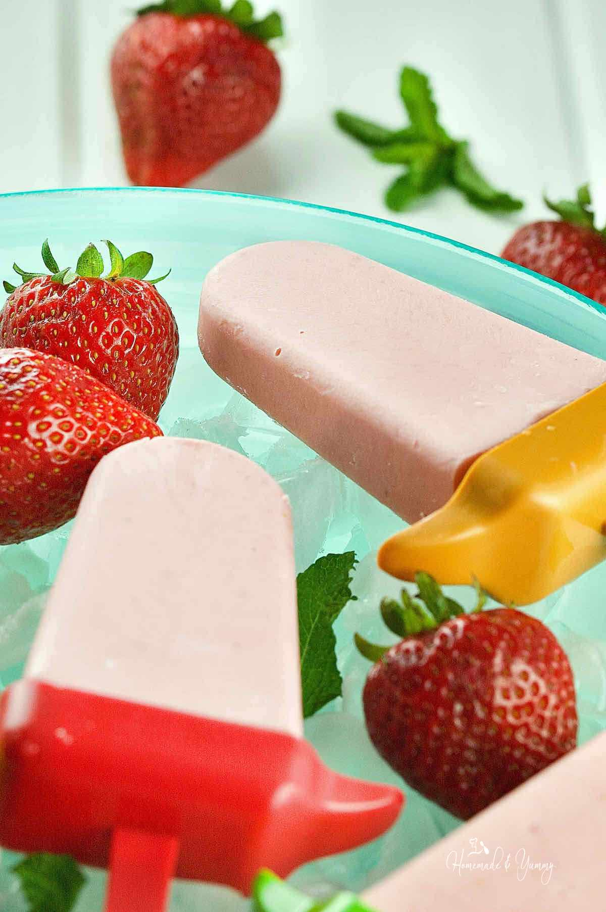 Creamy strawberry cheesecake popsicles on a bed of ice in a bowl.