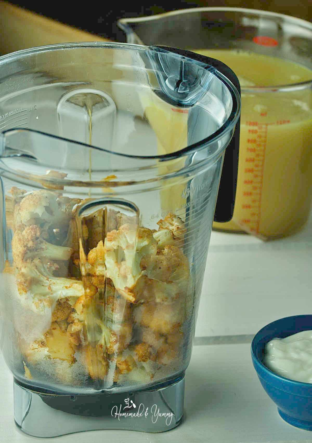Pieces of roasted cauliflower in a blender.